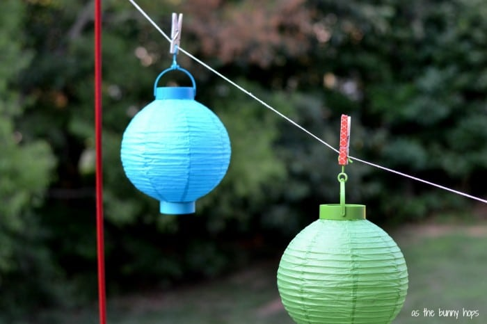 Easily hang paper lanterns from your deck with tomato stakes and twine.