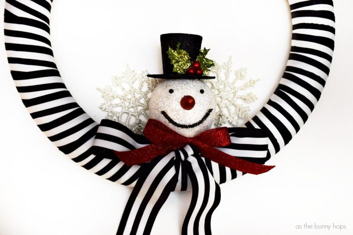Step up your outdoor Christmas decor with an adorable black and white snowman wreath and some easy light hanging tips!