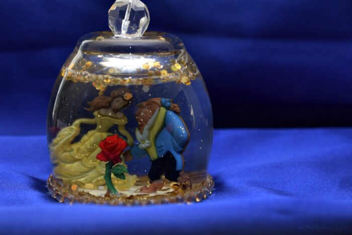 Make an easy and adorable DIY Beauty and the Beast Snow Globe with decorative buttons!