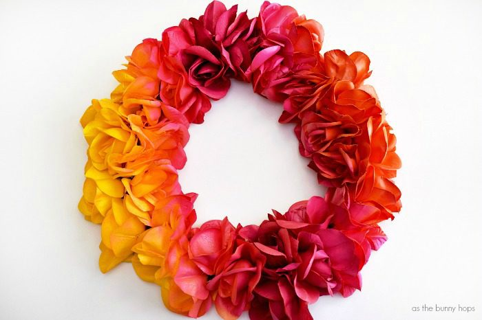 Make your own DIY ombré painted wreath for under $10! All you need is a glue gun, some silk flowers, and ringer flyer and some spray paint!